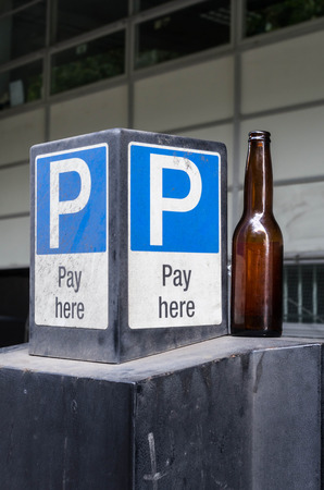 drink responsibly: The car park beside him an empty bottle of beer Stock Photo