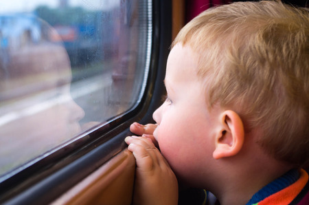 Small boy traveling by train, his face reflected in the glass photo