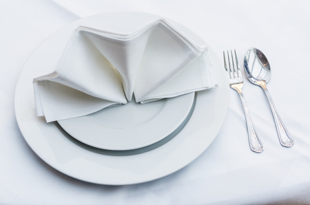 arranging chairs: Empty served restaurant table with white tablecloth