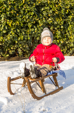 3 year old: 3 year old boy in red jacket sitting on a sleigh
