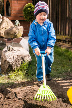 A little boy doing spring yard work photo