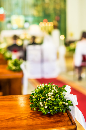 pews: Church pews decorated with bouquets, during the wedding ceremony