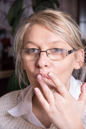 licking finger: A adult caucasian woman licking her finger