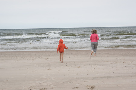 a mother and son plauing at a beach during windy day photo