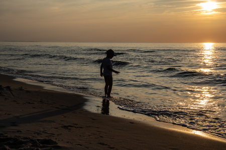 A shape of boy at the beach during sunset