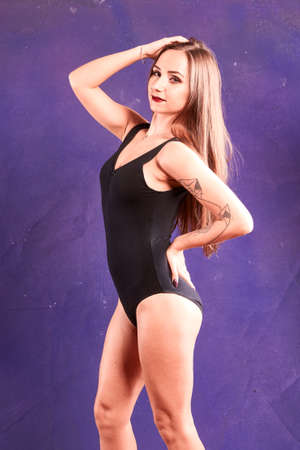 A caucasian girl, dancer, weread black body. violet baclground 스톡 콘텐츠