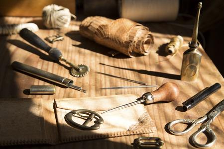 Lederhandwerk Tools auf einem hölzernen Hintergrund