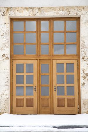 manacle: Massive oak door on a marble facade