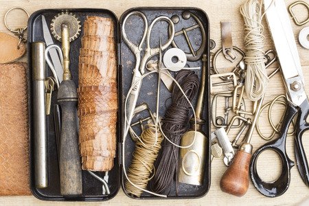 sewing item: Leather craft tools in the vintage metal box Stock Photo
