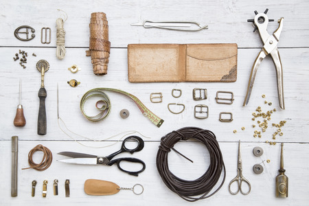 tool bag: Leather craft tools and utensils on a white wooden background