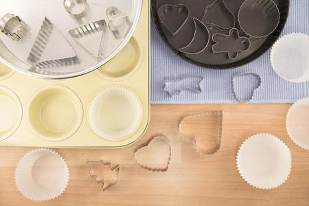 Metal pots and cake molds on a wooden background photo