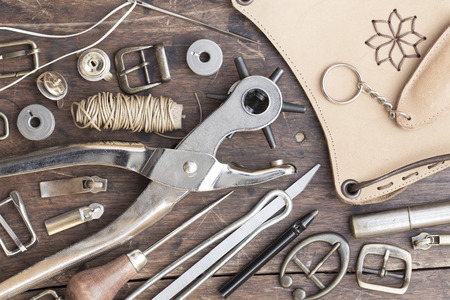 sew tags: Leather craft tools, thread and buckles on a wooden background