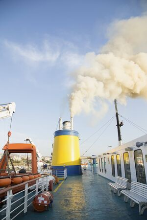 starboard: Deck on a catamaran ship with the smoke from the engine