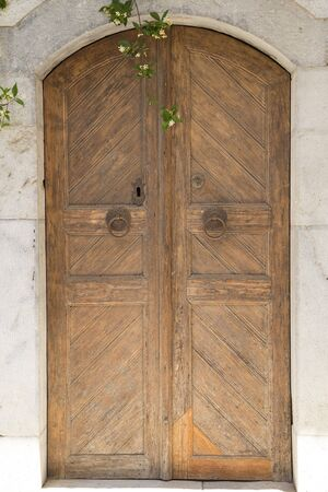 manacle: An old wooden door on a marble facade Stock Photo