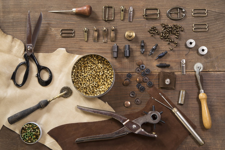 Leather craft tools on a wooden background