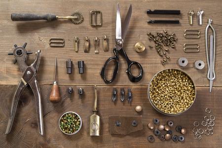 coser: Herramientas del arte del cuero sobre un fondo de madera