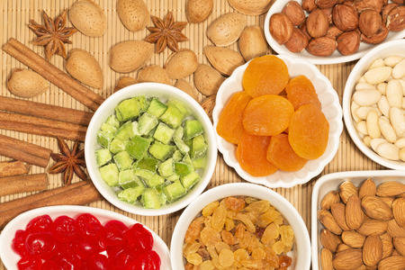 apricot kernels: Almond, hazelnuts and dried fruits in white porcelain bowls