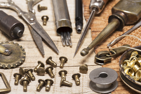 buckles: Leather craft tools, buckles and a snake skin Stock Photo