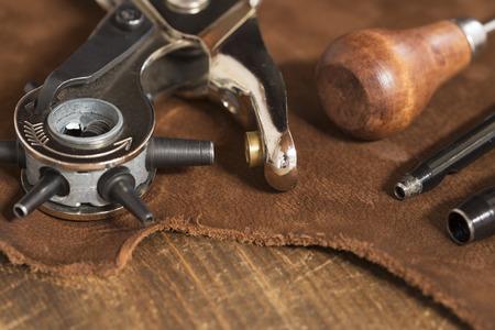coser: Herramientas de artesanía de cuero sobre un fondo de cuero marrón Foto de archivo