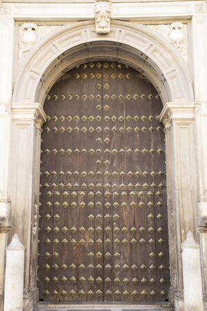 portones de madera: Masiva puerta de madera en una fachada decorativa de m�rmol