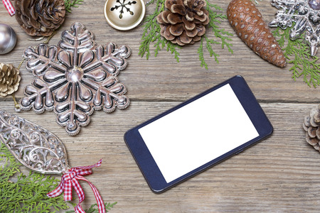 mobile phone: Mobile phone and the Christmas decoration on a wooden background Stock Photo