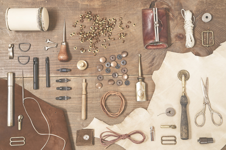 leather belt: Leather craft tools on wooden background - toned image
