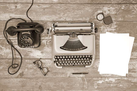 antique telephone: Vintage telephone and typewriter on a wooden background - toned image Stock Photo