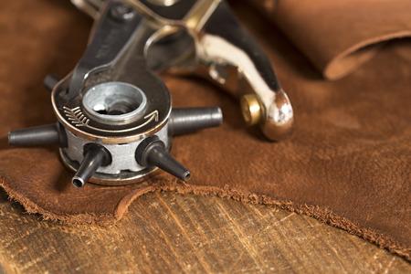 Kožený řemesla punč na kusu kůže Reklamní fotografie