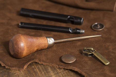 Leather craft tools and rivets on a leather background Standard-Bild