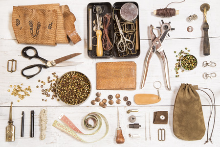 wood craft: Leather craft tools on white wooden background