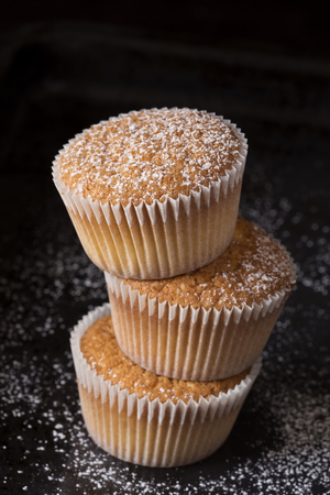 Three muffins sprinkled with the powder sugar Stock Photo