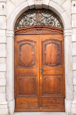 fasade: Massive oak decorative door on marble fasade Stock Photo
