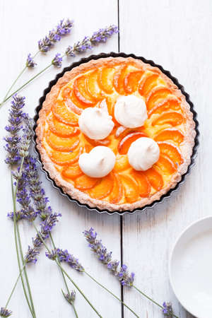 Apricot pie with lavender on white wooden table