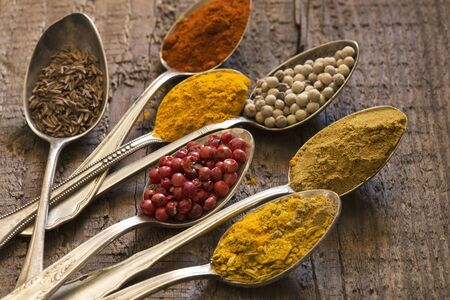 grunge silverware: Various spices in the vintage silver spoons Stock Photo