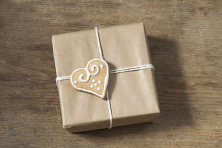 wrapped present: Brown paper wrapped present with gingerbread heart Stock Photo