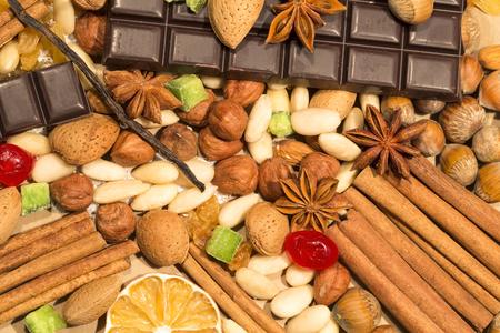 avellanas: Almendras, avellanas y especias con el chocolate como fondo Foto de archivo