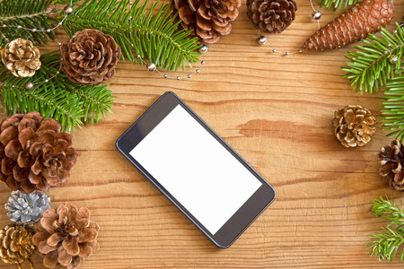 pinecones: Christmas decoration with the mobile phone on wooden background Stock Photo