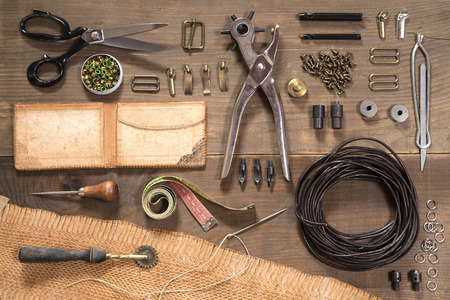 Leather craft tools on wooden background