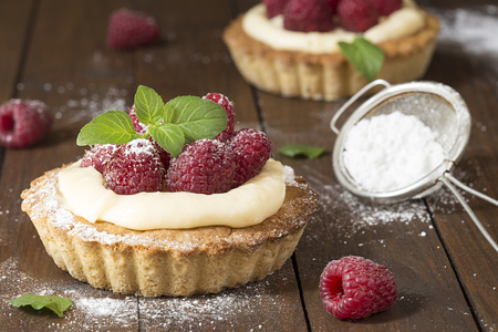 Raspberry tarts with mint and powdered sugar