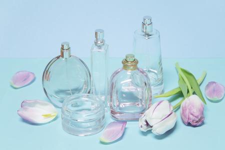 Bottiglie di profumo e tulipani su sfondo blu Archivio Fotografico - 74338601
