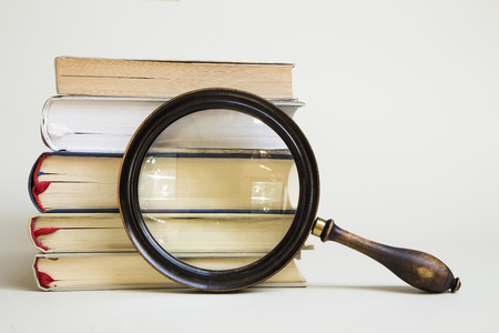 Vintage magnifying glass and stack of books