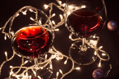 Two glasses of red wine with a light garland 写真素材