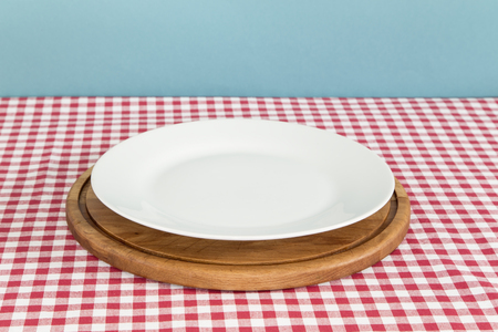 White plate and a cutting board on a table