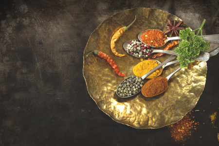 Spices in vintage silver spoons on brass plate