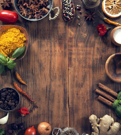 Various herbs and spices on grunge wooden background from above