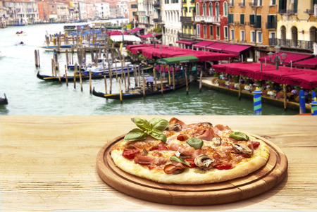 Rustic pizza on wooden table with Venice background Archivio Fotografico - 123223181