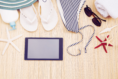 Woman's beach accessories with a black tablet Stock fotó