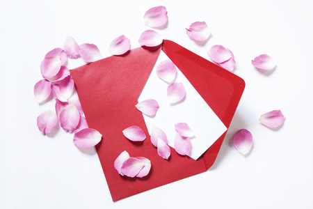 Red envelope with a blank note and rose petals Reklamní fotografie