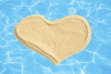Sand heart on blue water background Banco de Imagens