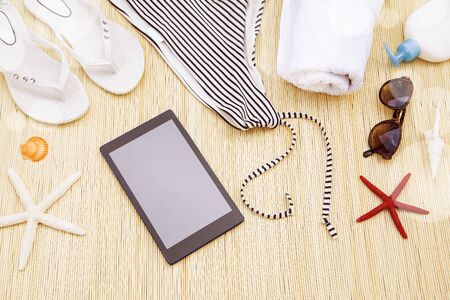 Woman`s beach accessories with a tablet